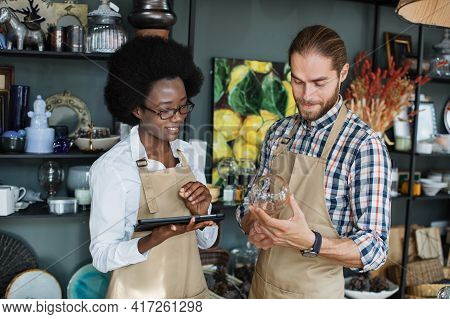 Beautiful Saleswoman Typing On Digital Tablet While Bearded Seller Holding Ceramic Cup. Multiethnic