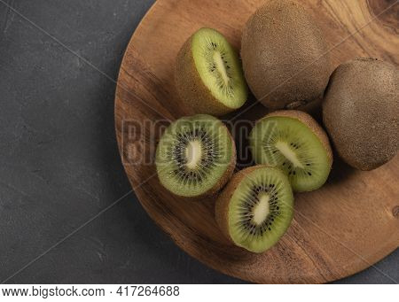 Top View Of Sliced Fresh Kiwi Fruit In Wooden Plate On Kitchen Table With Whole Kiwi Fruit. Close Up