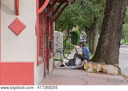 New Orleans, La - August 20: Man Repairs Bicycle Tire On Sidewalk On August 20, 2020 In New Orleans,