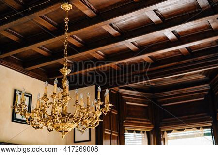 Gold Chandelier On A Chain Under A Wooden Ceiling.