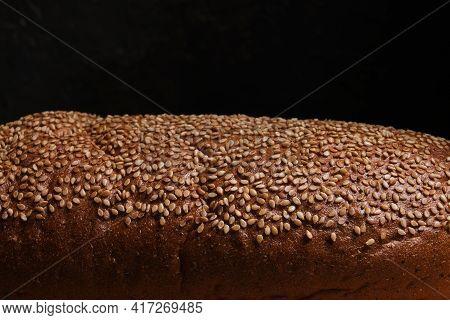 Bread Crust Is Sprinkled With Sesame Seeds, Light On Top, Black Background.dark Food