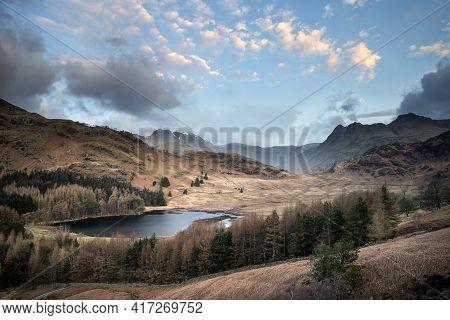 Stunning Sunrise Landscape Image Of Blea Tarn In Uk Lake District With Langdales Range In Background