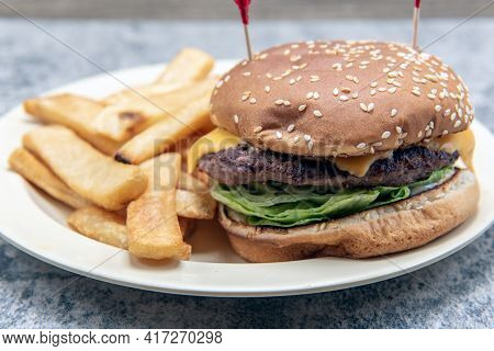 Cheeseburger Stacked High With Melted Cheese And Fillings Combined With A Thick Serving Of Steak Fri
