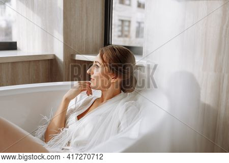 Morning Of The Bride. Happy Beautiful Young Woman Is Wearing In A White Long Veil, Robe And Underwea