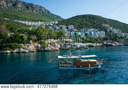 Kas, Turkey - 17 October, 2019: Daily boat trip and privat tour boat with tourists in Kas marina with coastal town on hills, Popular tourist destination on Turkish Mediterranean coast