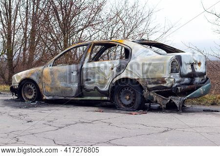 Burned Car After An Accident On The Asphalt Road. Side View. Arson Of A Car, Criminal Showdowns
