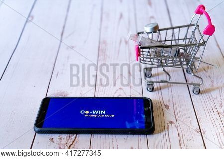 Mobile Phone With Co-win App Logo On The Screen With A Small Shopping Cart With A Syringe And Vial S
