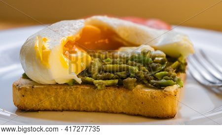 Fresh Homemade Delicious Sandwich With Avocado And Poached Egg And Cut Yolk On A White Plate Closeup