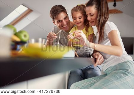 A young family having a good time after a breakfast in a cheerful atmosphere at home. Family, breakfast, together, home