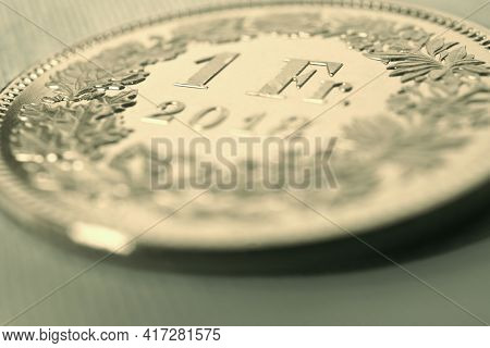 1 One Swiss Franc Coin Close-up. Light Yellow Background Or Wallpaper On An Economic, Business, Entr