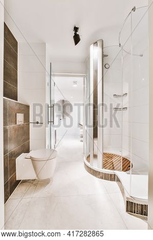 Narrow Walk Through Washroom With Glass Shower Cabin And Wall Hung Toilet In Apartment