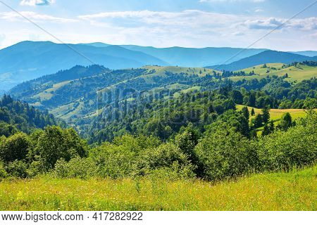 Countryside Landscape In Summer. Beautiful Nature Scenery With Meadows On The Hills Rolling In To Th