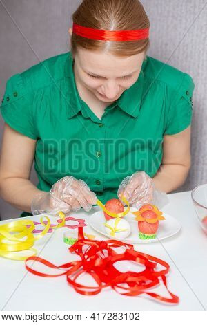 Female Hands In Pastry Chef's Gloves And A Green Blouse Decorate Eggs For The Holiday