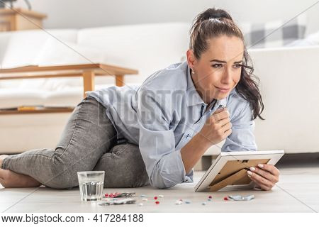 Young Woman Overdoses Herself By Pills On The Living Room Floor Holding A Picture Of Someone Whom Sh