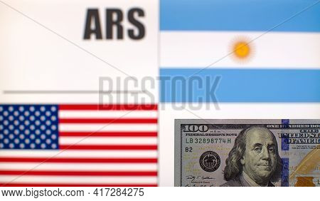 100 Us Dollars Banknote On Blurred Background Of Argentina And Usa Flags And Currency Code Of Argent