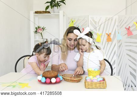 Mom And Daughters Decorate A Basket For Easter