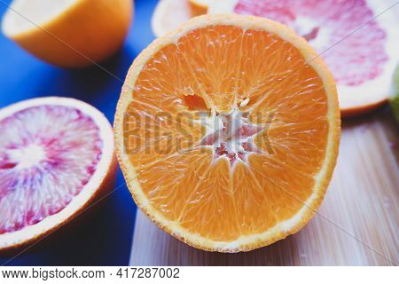 In The Photo, Sliced Fruits, A Knife And A Cutting Board: Oranges, Tangerines, Lemon, Lime, Grapefru