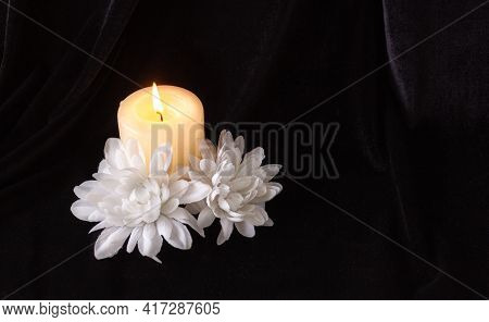 The Concept Of Remembrance, Funerals, And Condolences. Candle And White Flowers, Free Space For Text