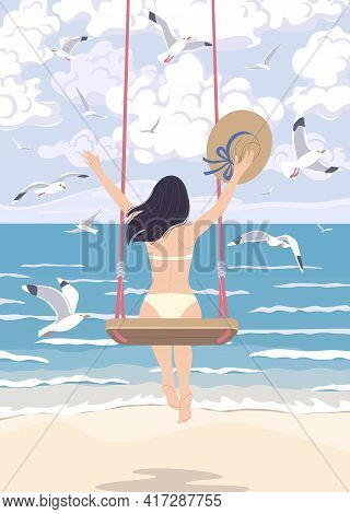 Young Woman With Long Dark Hair Swinging On A Swing At The Sea Coast. Dreamy Girl Holding Straw Hat,