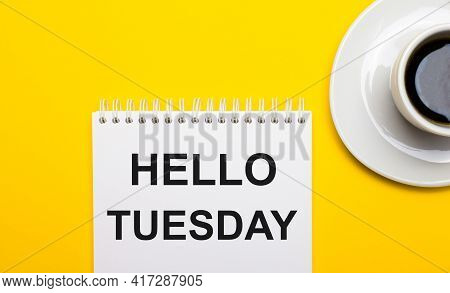 On A Bright Yellow Background, A White Cup With Coffee And A White Notepad With The Words Hello Tues