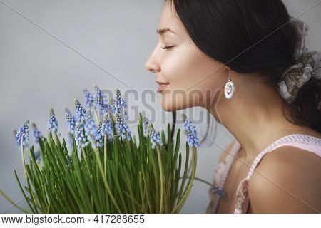 Beautiful Young Woman Smelling Bouquet Of Spring Flowers With Closed Eyes. Sensual Romantic Mixed Ra