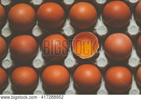 Whole Brown Chicken Eggs In Recycled Paper Tray And Open One With Yolk