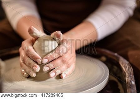 Hands And A Piece Of Clay On A Potter's Wheel. Hands Of A Woman Potter Close-up With Selective Focus