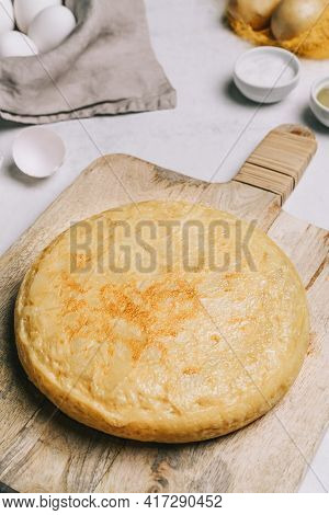 Closeup Scene Of Potatos Omelette On A Rustic Wooden Table, A Basket Of White Eggs, Olive Oil And Sa