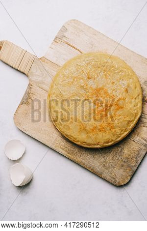 Aerial View Of A Potato Omelette On A Retro Wooden Table And An Eggshell On A White Marble Backgroun