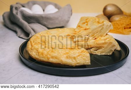Potatoes Omelette Cut Into A Black Round Plate On A Yellow Background And A White Table With A Net O