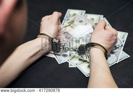 Man In Handcuffs With Money And Drugs On Dark Background. The Concept Of Punishment For Possession,