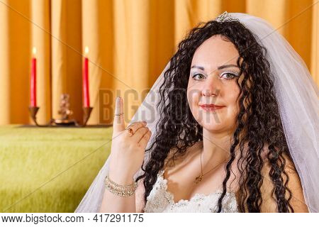 A Jewish Newlywed In A White Wedding Dress With A Veil Sits At A Table With Flowers After The Chuppa