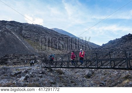 Tongariro New Zealand - March 27 2021; Trampers Cross Small Bridge In Morning Light Framed By Volcan