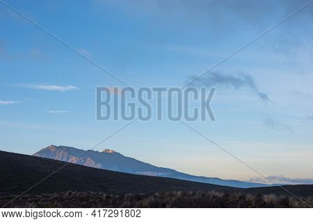 Sun Rising Over Mount Ruapehu Beyond The Silhouette Foreground In Tongariro National Park.