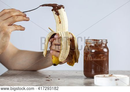 A Caucasian Woman Is Spreading A Spoon Of Nut Flavored Sweet Cocoa Spread On A Peeled Banana For A S