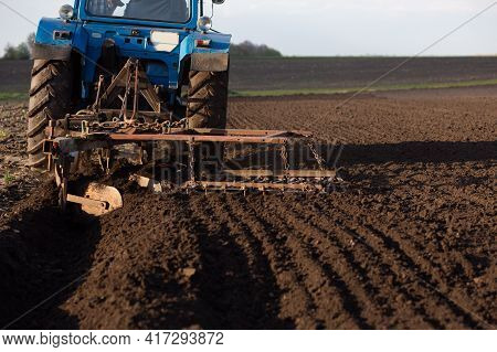 Tractor Plow That Plows The Land Close-up. Place For Your Text