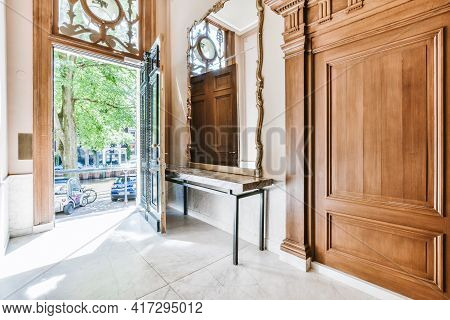Large Vintage Mirror Placed On Table Near Open Entrance Door In Hall Of Old Stone Building With Wood