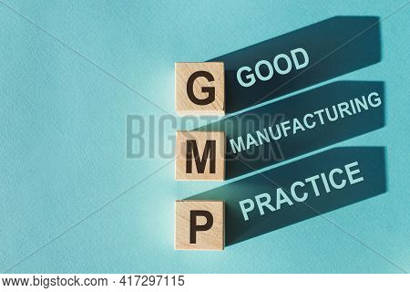 Wooden Cubes Building Word Gmp - Abbreviation Of Good Manufacturing Practice On Light Blue Backgroun