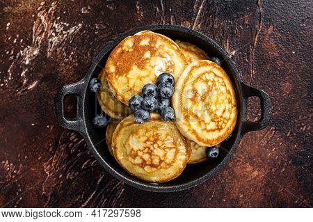 Fried Pancakes With Fresh Blueberries And Maple Syrup In A Pan. Dark Background. Top View
