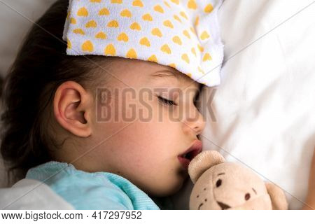 Authentic Portrait Sick Cute Caucasian Little Preschool Baby Girl In Blue Sleep With Compress On For