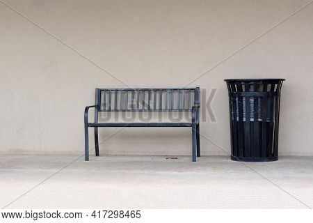 Urban Bench And Trash Can In Sidewalk Against Light Brown Office Wall