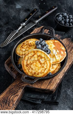 Pancakes With Fresh Blueberries And Maple Syrup In A Pan. Black Background. Top View