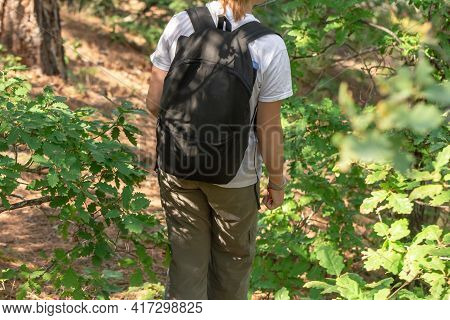 Use Of Backpack Travel Small Backpack During Short Trips In Nature. Teenager Girl Walking Through Fo