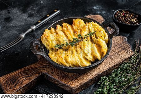 Potato Gratin Dauphinois In A Pan. Black Background. Top View