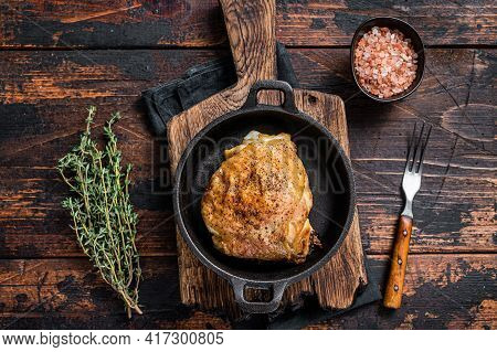 Baked Chicken Thigh In A Pan With Rosemary And Salt. Dark Wooden Background. Top View