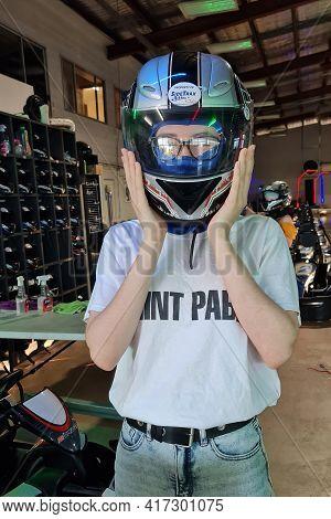 Mackay, Queensland, Australia - April 2021: Young Woman Puts On Her Helmet Ready For Go Kart Racing