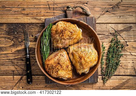Roasted Chicken Thighs In A Wooden Plate With Rosemary And Herbs. Wooden Background. Top View