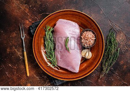 Raw Poultry Turkey Breast Fillet Meat In A Rustic Plate With Rosemary And Thyme. Dark Background. To