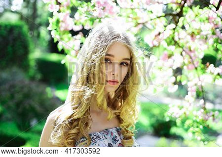 Tenderness Concept. Girl On Dreamy Face, Tender Blonde Looks At Camera, Nature Background, Defocused