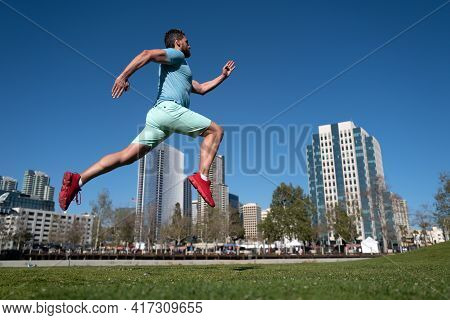 Athletic Young Man Running In City. Dynamic Jumping Movement. Young And Active Jogger Running. Urban